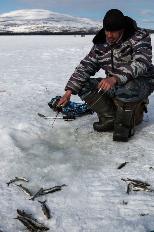 Fishing on the frozen lakes in Artic Russia seems to be a case of a little round hole drilled through the ice with an augar, a tiny plastic fishing rod and line that you jiggle up and down quickly all the time, plenty of smokes and the eskie (cooler bag).  Everyone up here seems to chain smoke!